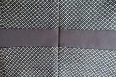 Bruine streep die aan de grijze stof wordt genaaid Stock Afbeeldingen