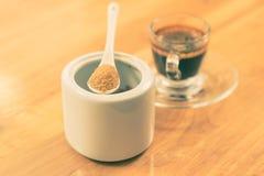 Bruine suiker in een witte ceramische lepelzitting bovenop witte cer Royalty-vrije Stock Foto