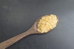 Bruine suiker met lepel Stock Afbeelding