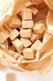 Bruine suikerkubussen in suikerdocument zak Stock Foto