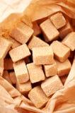 Bruine suikerkubussen in suikerdocument zak Royalty-vrije Stock Afbeeldingen