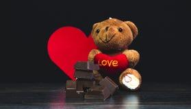 Bruine teddybeer, yummy chocolade en de zwarte achtergrond en dag van de valentijnskaart royalty-vrije stock foto's