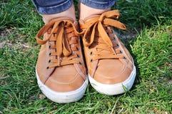 Bruine tennisschoenen op groen gras royalty-vrije stock foto