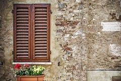 Bruine vensterblinden in een rustieke muur stock afbeeldingen