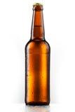 Bruine volledige fles bier met dalingen die op wit worden geïsoleerdn royalty-vrije stock foto