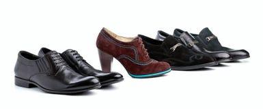 Bruine vrouwelijke laars tussen zwarte mannelijke schoenen Stock Afbeelding