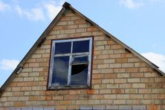 Bruine zolder van een baksteenhuis met een gebroken venster royalty-vrije stock afbeelding