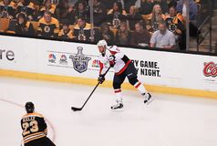 Chris Kelly and Mike Green. Bruins forward Chris Kelly 23 skates in front of a pass from Capitals defenseman Mike Green 52 stock photography