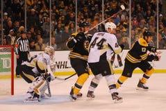 Bruins v. Penguins, NHL Hockey. Boston Bruins forward Benoit Pouliot tries to set up camp between Pittsburgh Peguins defenseman Brooks Orpik and goalie Marc Royalty Free Stock Image