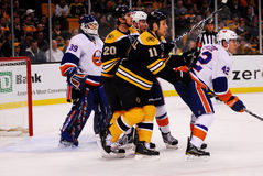 Bruins vs. New York Islanders NHL. Boston Bruins forwards Gregory Campbell (11) and Daniel Paille (20) try to create a screen in front of New York Islanders royalty free stock images