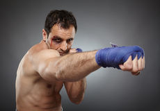 Bruised fighter punching Royalty Free Stock Images