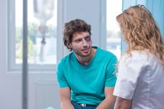Bruised man flirting with nurse. Bruised men flirting with nurse in treatment room stock photo