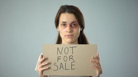 Bruised woman holding not for sale sign, human trafficking, sexual assault. Stock footage stock video footage