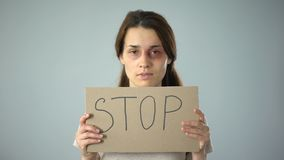 Bruised woman holding stop sign, call for help, assistance to violence victim. Stock footage stock footage