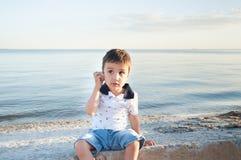 Bruit de écoute mignon de petit garçon de mer dans la coquille photographie stock libre de droits