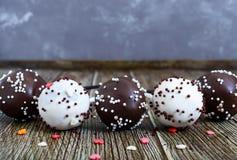 Bruits de gâteau Bonbons doux dans le lustre blanc et noir de chocolat, sur un bâton sur un fond en bois photos libres de droits