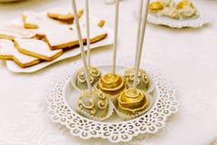 Bruits de gâteau décorés du chocolat d'or et gris sur le carv blanc Photo stock
