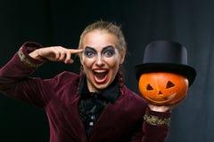 Bruja alegre de la muchacha en Halloween con la calabaza Foto de archivo