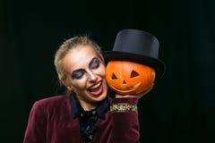 Bruja alegre de la muchacha en Halloween con la calabaza Imagenes de archivo