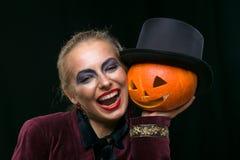 Bruja alegre de la muchacha en Halloween con la calabaza Fotos de archivo