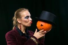 Bruja alegre de la muchacha en Halloween con la calabaza Imagen de archivo libre de regalías