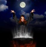 Bruja con la caldera en fondo del cielo nocturno Imagen de archivo libre de regalías