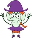 Bruja dañosa de Halloween que presenta y que sonríe malévolo Imagen de archivo