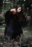 Bruja de Halloween en una mujer joven hermosa del bosque oscuro en traje de las brujas Diseño del arte de Halloween Fondo del hor Foto de archivo libre de regalías