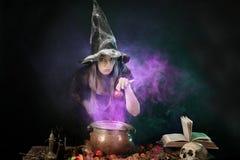 Bruja de Halloween que cocina una poción en una caldera Imagen de archivo