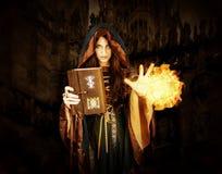Bruja de Halloween que sostiene el libro mágico con las runas que hacen magia Imágenes de archivo libres de regalías