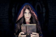 Bruja de Halloween que sostiene el libro mágico de encantos imágenes de archivo libres de regalías