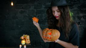 Bruja de la muchacha en Halloween en a, sosteniendo la calabaza con una vela y un bastidor ardientes un encanto Jack-o-linterna almacen de metraje de vídeo
