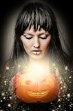 Bruja de la mujer que hace magia a la calabaza Imagen de archivo libre de regalías