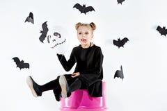 Bruja de la niña en vestido negro sobre los accesorios mágicos Halloween, la tarde del estudio Foto de archivo