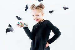 Bruja de la niña en vestido negro sobre los accesorios mágicos Halloween, la tarde del estudio Foto de archivo libre de regalías