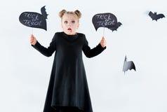 Bruja de la niña en vestido negro sobre los accesorios mágicos Halloween, la tarde del estudio Imagenes de archivo