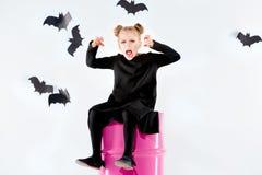Bruja de la niña en vestido negro sobre los accesorios mágicos Halloween, la tarde del estudio Fotografía de archivo