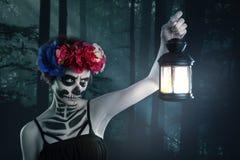 Bruja de Víspera de Todos los Santos Mujer hermosa que lleva encanto del bastidor de la máscara del muerte de santa fotografía de archivo