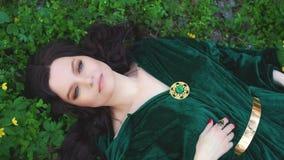 Bruja en un impermeable esmeralda, mago con los pelos rizados largos en bosque de la primavera almacen de video
