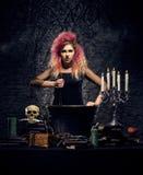 Bruja hermosa que hace brujería en un fondo ahumado Imagen de Halloween Fotos de archivo