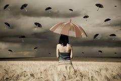 Bruja joven en el campo de trigo con el paraguas en ra Imágenes de archivo libres de regalías