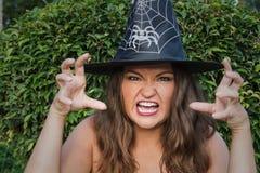 Bruja joven en sombrero negro que grita en la cámara Foto de archivo