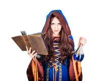 Bruja joven hermosa de Halloween que lee el libro mágico y sostenerse imagen de archivo