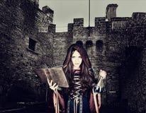 Bruja joven hermosa de Halloween que lee el libro mágico y sostenerse imagenes de archivo