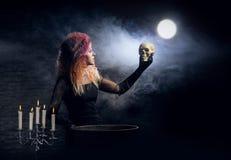 Bruja joven que hace brujería en una mazmorra de Hallowen Imágenes de archivo libres de regalías