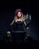 Bruja joven que hace brujería en una mazmorra de Hallowen Imagen de archivo libre de regalías