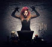 Bruja joven que hace brujería en una mazmorra de Hallowen Fotos de archivo libres de regalías