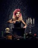 Bruja joven que hace brujería en una mazmorra de Hallowen Fotos de archivo