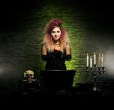 Bruja joven que hace brujería en una mazmorra de Hallowen Imagenes de archivo