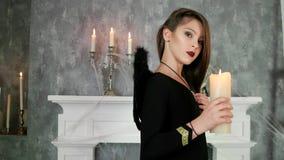 Bruja joven que lleva a cabo la vela, celebración del partido de Halloween, muchacha que lleva el traje oscuro de los ángeles, ma almacen de metraje de vídeo